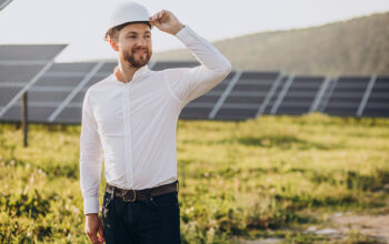 Young architect standing by solar panels